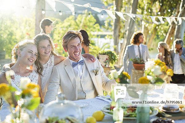 Junges Paar und Brautjungfer bei der Hochzeitsfeier im Hausgarten
