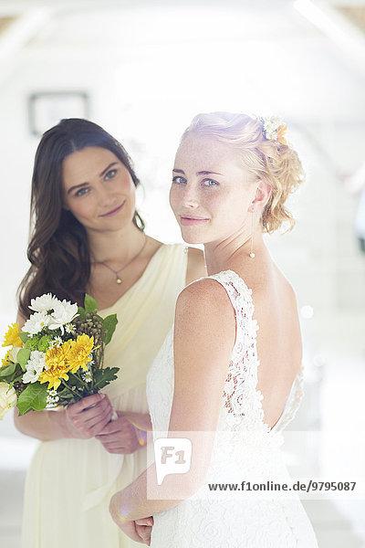 Portrait von Braut und Brautjungfer mit Blumenstrauß im heimischen Zimmer