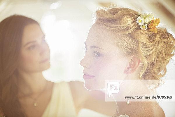 Portrait der Braut mit Brautjungfer im Hintergrund im Wohnzimmer
