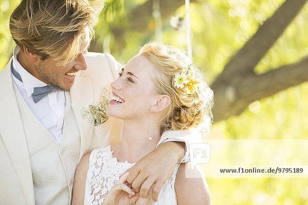 Bräutigam umarmt Braut im Hausgarten
