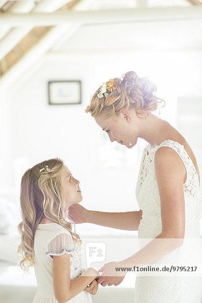 Braut im Gespräch mit der Brautjungfer im Wohnzimmer