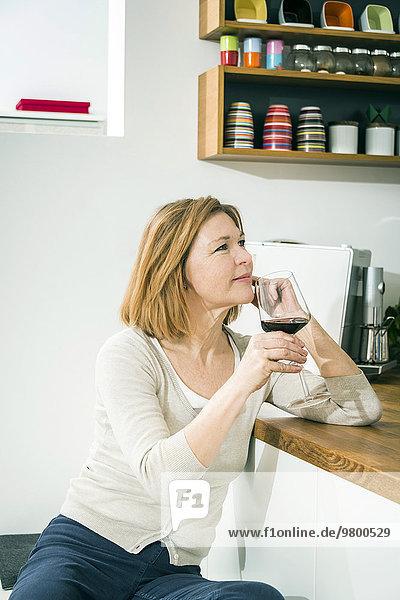 Senior Senioren Frau Küche Rotwein trinken