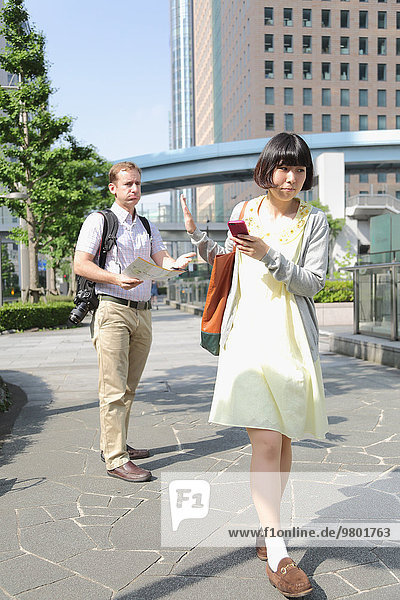 Young Japanese girl escaping from foreign tourist asking for help