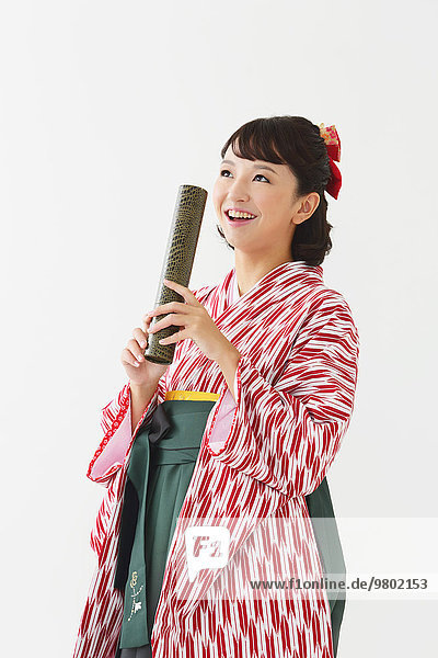 Young Japanese girl in a kimono against white background