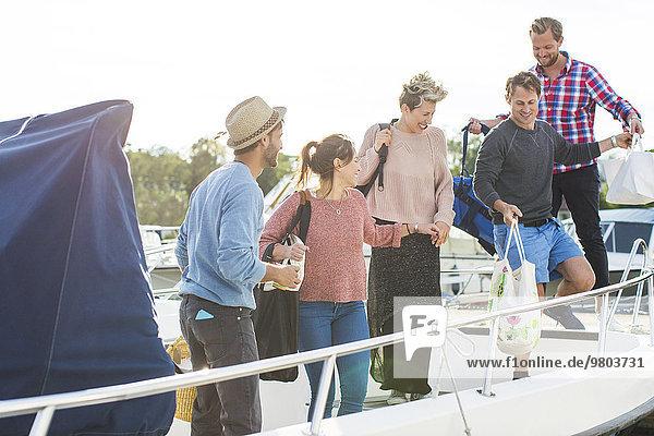 Glückliche Freunde beim Einsteigen in die Yacht gegen den Himmel