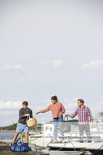 Freunde an Bord einer Yacht gegen den Himmel