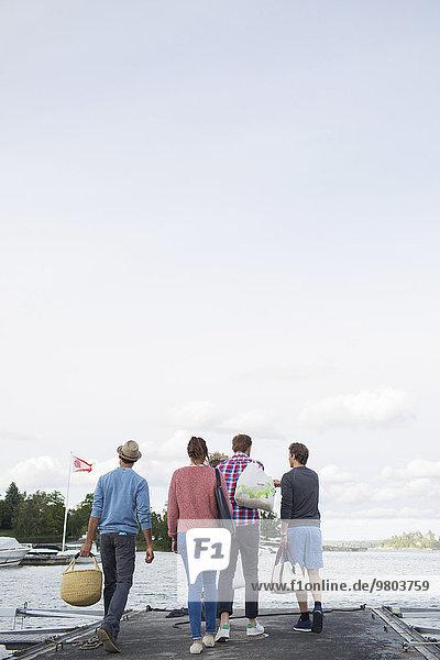 Durchgehende Rückansicht von Freunden  die auf dem Pier gegen den Himmel gehen.