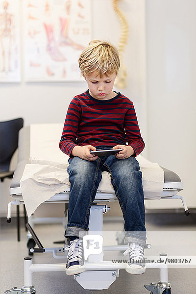Boy using smart phone on examination table in orthopedic clinic
