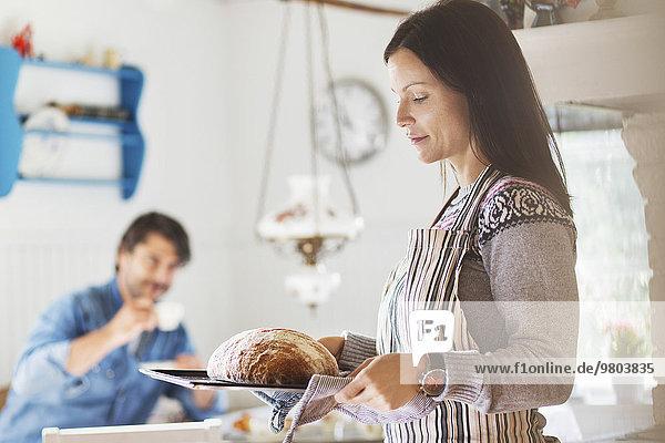 Frau mit frisch gebackenem Brot im Tablett und Mann im Hintergrund zu Hause