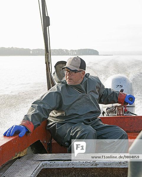 Fischer schaut weg  während er im Boot auf See sitzt.