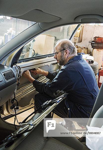 Side view of senior male mechanic fixing car door at garage