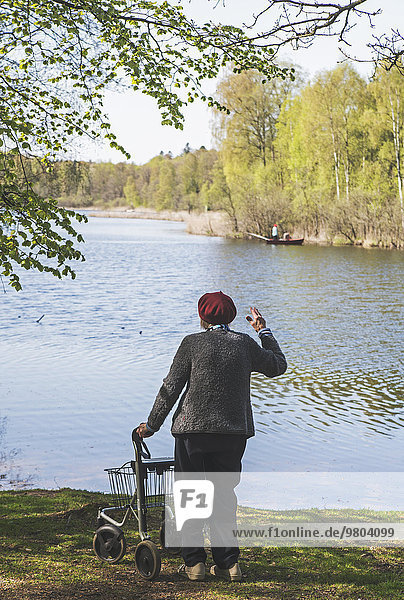 Rear view of senior woman with walker waving to fisherman in boat on lake