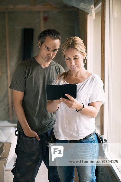 Paar mit digitalem Tablett im renovierten Haus