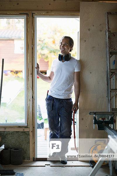 Volle Länge des lächelnden Mannes  der sich in der Tür des zu renovierenden Hauses lehnt.