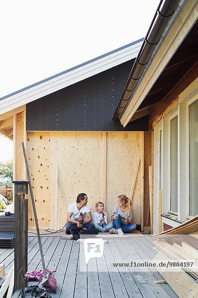 Glückliche Familie mit Bauwerkzeugen vor dem Haus