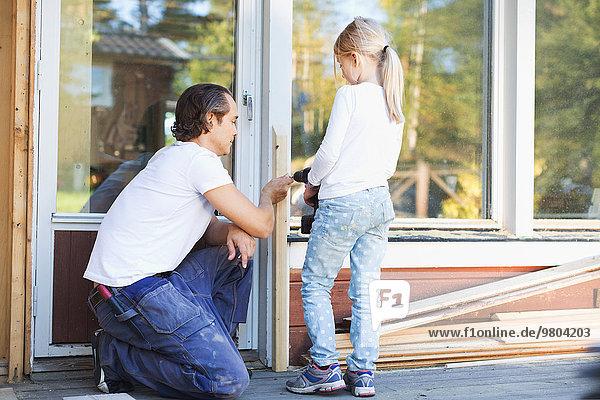 Vater hilft Mädchen bei der Verwendung von Akkuschrauber auf dem Rahmen während der Hausverbesserung