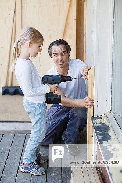 Vater hilft Mädchen bei der Verwendung von Akkuschrauber bei der Verbesserung zu Hause