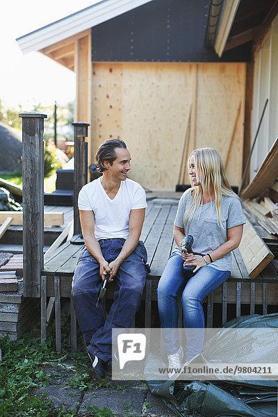 Glückliches Paar  das sich außerhalb des Hauses während der Hausverbesserung ansieht.