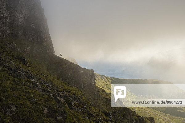 Fernsicht des Mannes  der auf einer Klippe gegen den bewölkten Himmel steht.