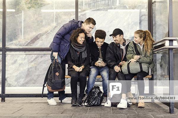 Gruppe von Studenten  die gemeinsam an der U-Bahn-Station ein Smartphone benutzen