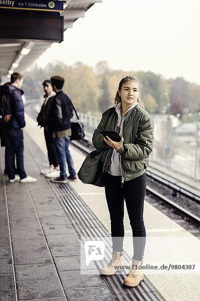 Volle Länge der Studentin mit digitalem Tablett an der U-Bahn-Station mit Freunden im Hintergrund