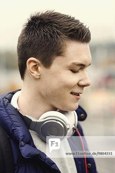 Lächelnder Student mit Kopfhörer um den Hals im Freien
