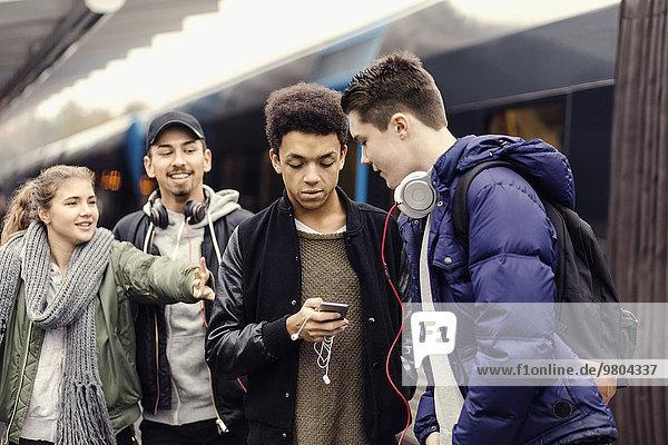 Junge Frau ruft Freunde über Smartphone in der U-Bahn-Station an