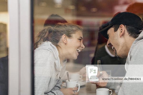 Blick auf das glückliche junge Paar mit Smartphone im Cafe durch Glas