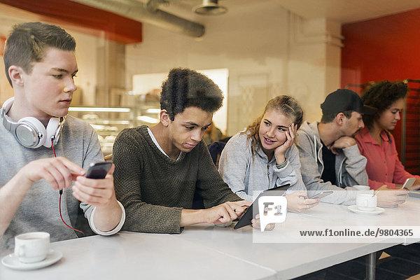 Freunde  die Technologien am Tisch in der Cafeteria nutzen