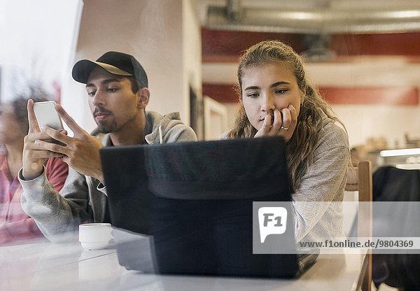 Blick auf die Studenten  die Technologien am Kaffeetisch nutzen