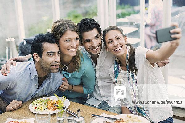 Lächelnde Geschäftsleute  die Selfie im Cafe nehmen