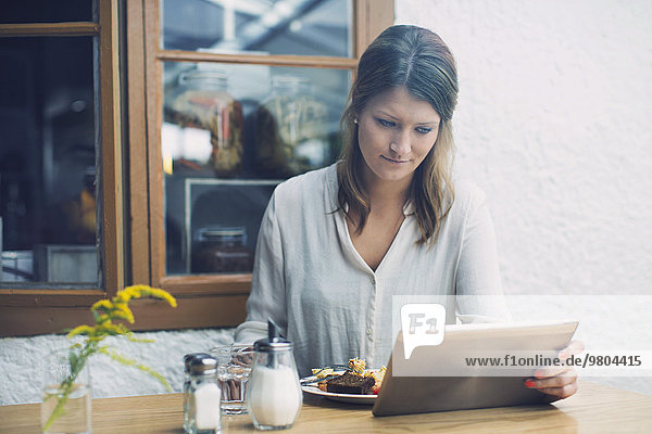 Frau mit digitalem Tablett beim Mittagessen im Cafe