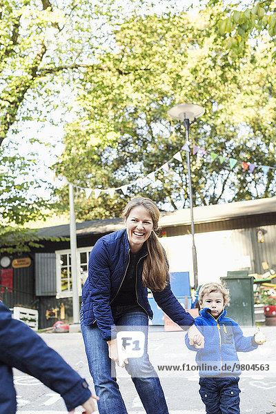 Glückliche Lehrerin mit Kindern außerhalb des Kindergartens Glückliche Lehrerin mit Kindern außerhalb des Kindergartens