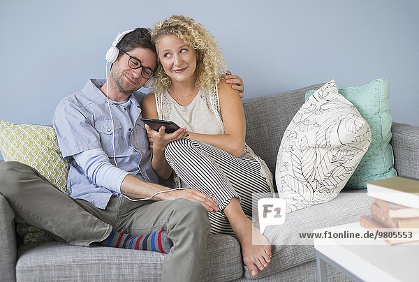 Couple sitting on sofa listening to music