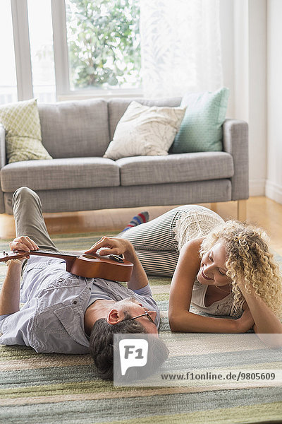 Couple lying on floor playing ukulele