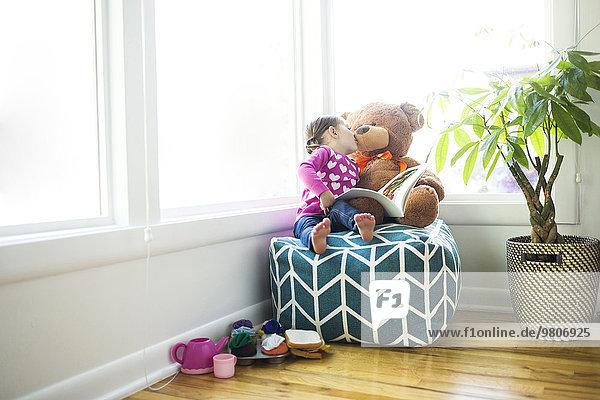 Girl (4-5) kissing her teddy bear on bean bag