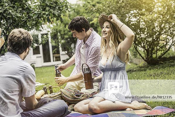 Freunde sitzen beim Picknick im Garten