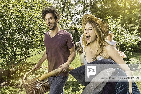 Junges Paar  das im Garten spazieren geht und sich auf ein Picknick vorbereitet.