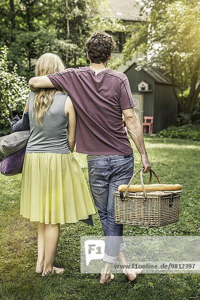 Paar Tragekissen und Picknickkorb im Garten