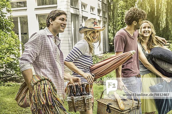 Freunde bereiten sich auf ein Picknick im Garten vor.