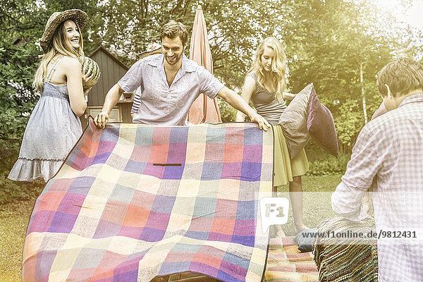 Mann öffnet Picknickdecke im Garten