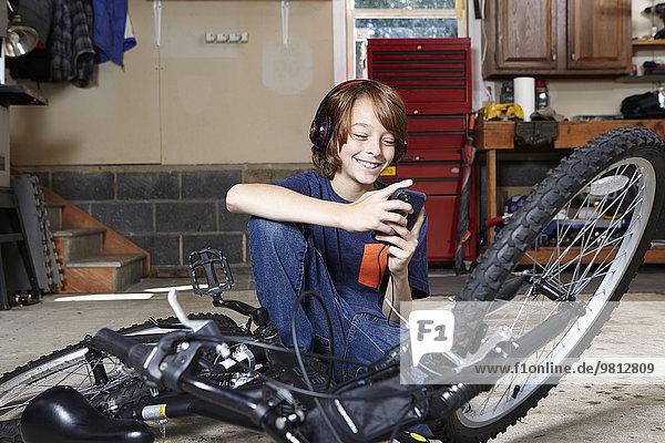 Boy in garage choosing music on smartphone