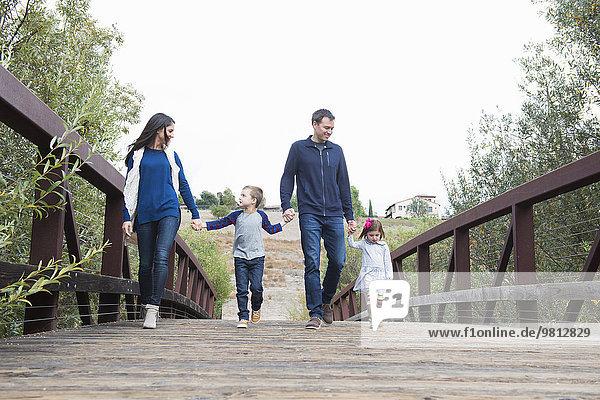 Paar und zwei Kinder schlendern Hand in Hand über die Parkbrücke