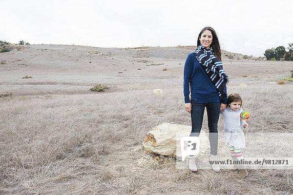Porträt einer mittleren erwachsenen Frau und Tochter in hügeliger Landschaft