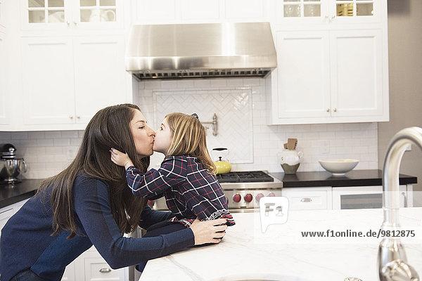 Mutter küsst Tochter in der Küche