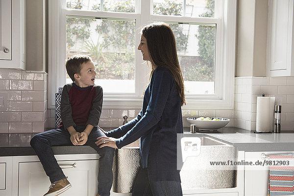 Mutter plaudert mit dem Sohn  der auf der Küchentheke sitzt.