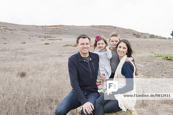 Porträt von Eltern und zwei Kindern  die auf einem Felsen sitzen
