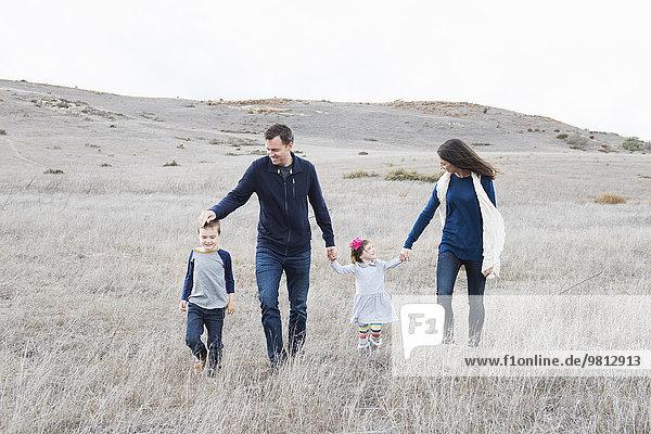 Paar und zwei Kinder beim Wandern in hügeliger Landschaft