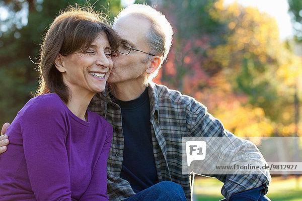 Senior man kissing wife on cheek in garden