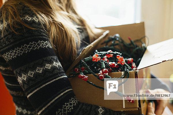 Frau mit Weihnachtsbeleuchtung im Karton
